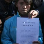 Qian Renfeng holds the judgment of innocence issued by the Yunnan Provincial Higher People's Court on December 21, 2015 (CFP)