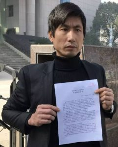 Wang Shenbing outside courthouse on December 22, 2016 holding prosecutors decision to dismiss his charges.